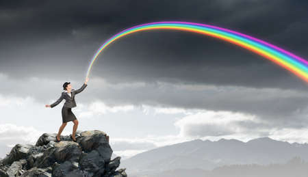 bowler: Young businesswoman in bowler hat and colorful rainbow in hand