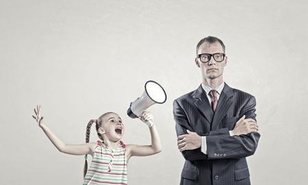 megafono: Ni�o gritando con el meg�fono al hombre indiferente adultos Foto de archivo