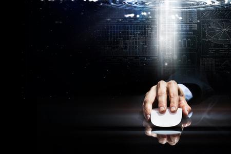 ワイヤレス コンピューターのマウスを使用して暗いデジタル背景にスーツのビジネスマンの手