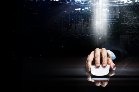 web marketing: Hand of businessman in suit on dark digital background using wireless computer mouse