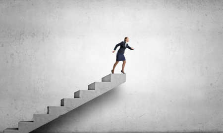 business development: Young businesswoman running up staircase representing success concept