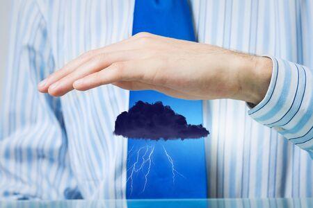company secrets: Hand of businessman protecting black raining cloud