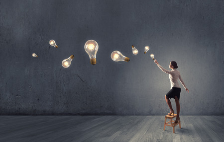 creativity and innovation: Back view of businesswoman standing on chair and reaching light bulb