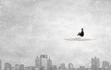 incapacity: Thoughtful young businesswoman sitting alone on cloud above city Stock Photo
