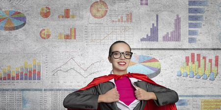 sales promotion: Young businesswoman in red cape acting like super hero