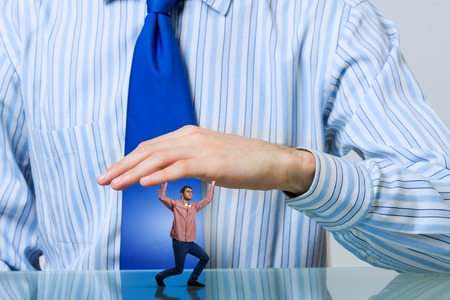claustrophobia: Young man under pressure of human big hand Stock Photo