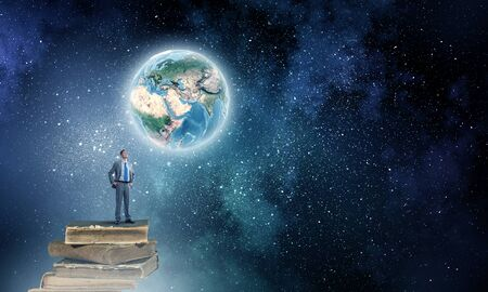 broaden: Young confident businessman with arms on waist standing on pile of old books. Elements of this image are furnished by NASA