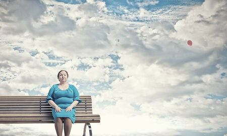 curvy woman: Middle aged stout woman in blue dress sitting on bench Stock Photo