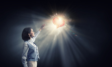 blinded: Young businesswoman blinded with light of heart going from above