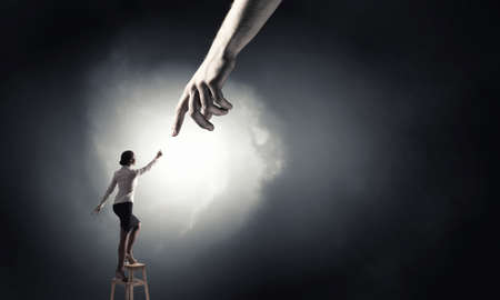 get help: Young woman standing on chair and reaching hand to get help Stock Photo