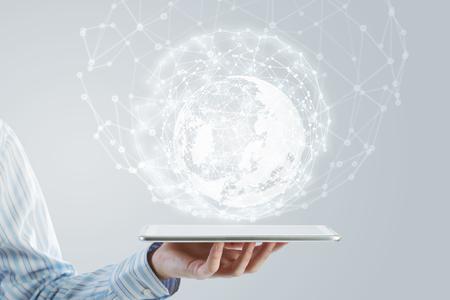 Zakenman die in hand tablet met de wereldwijde verbinding concept Stockfoto