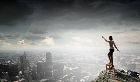 hands reaching: Businesswoman standing on chair and reaching hand to touch something Stock Photo
