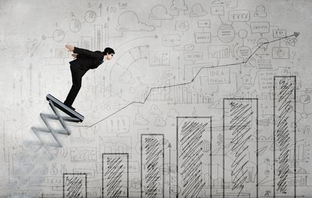 springboard: El hombre de negocios que salta en el trampolín como concepto de progreso