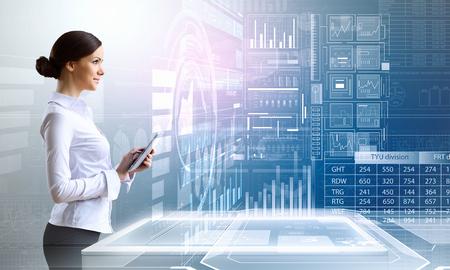 Nữ doanh nhân với máy tính bảng máy tính chống lại nền màu xanh công nghệ cao
