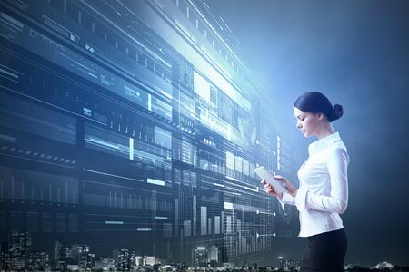 Imprenditrice con tablet pc contro high-tech sfondo blu Archivio Fotografico - 49043518
