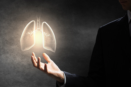lung bronchus: Male hand on dark background holding lungs symbol