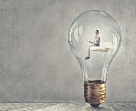 broaden: Young businessman inside of light bulb reading book
