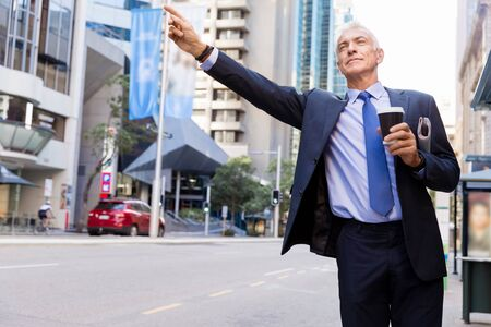 catching taxi: Businessman in suit catching taxi in city with cup of coffee in his hands