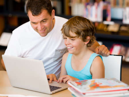netbook: Little boy and his father with laptop in library
