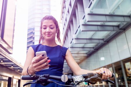 environmental issues: Young woman in business wear on bicycle and holding mobile phone