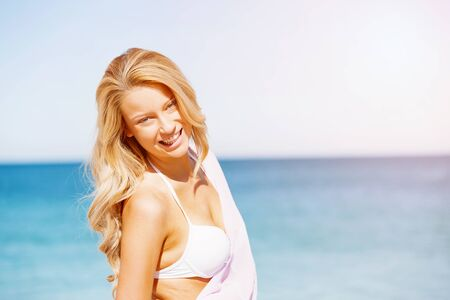 sun bathers: Portrait of young pretty woman in white bikini relaxing on sandy beach Stock Photo