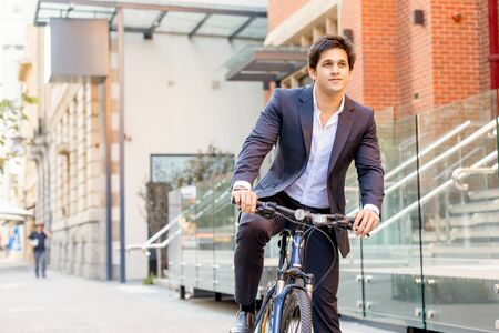 business lifestyle: Successful businessman in suit riding bicycle