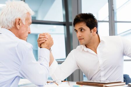 Handshake business: Two businessmen competeting arm wrestling in office Stock Photo