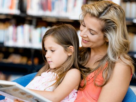 school book: Little girls with their mother reading books in library