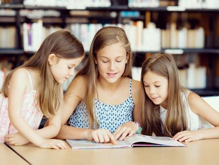 Kleine Mädchen lesen Bücher in der Bibliothek Lizenzfreie Bilder