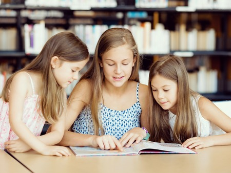 young: Little girls reading books in library Stock Photo