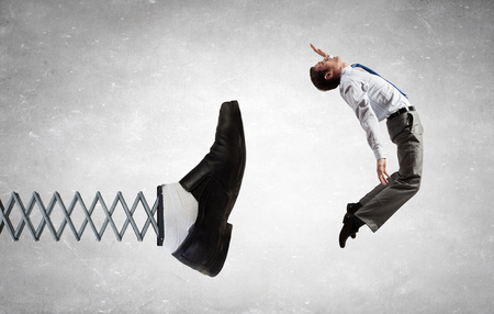 Businessman kicked by his boss foot on spring