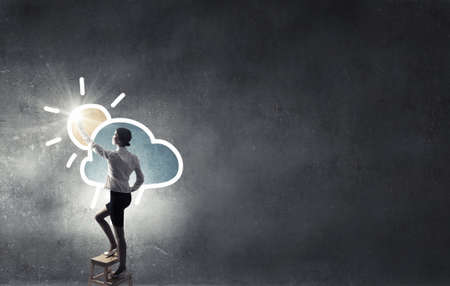 achieve: Businesswoman standing on chair and reaching cloud in sky