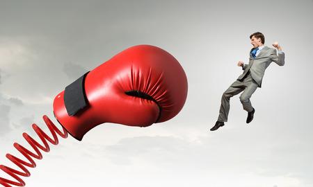 Fiatal elszánt üzletember harci bokszkesztyű a tavaszi