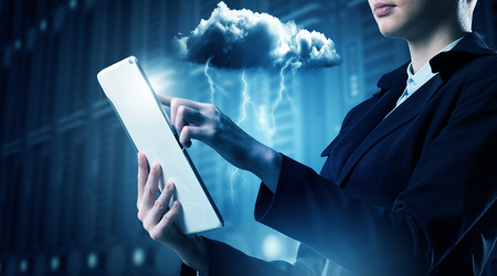cloud computer: Businesswoman with tablet pc against high tech background Stock Photo