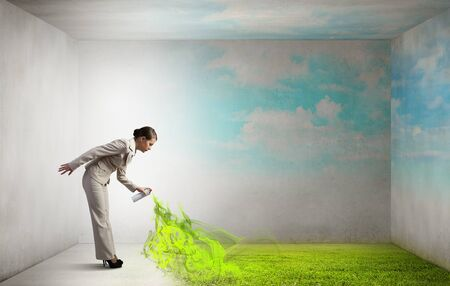 aerosol: Young businesswoman spraying green grass from aerosol balloon