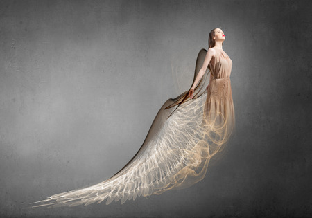 attractive angels: Attractive woman with angel wings on concrete background Stock Photo