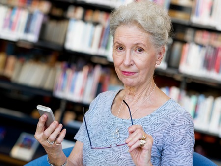 lady on phone: Elderly lady with mobile phone in library