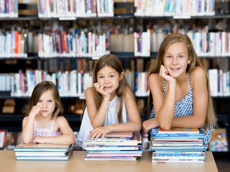 school friends: Little girls reading books in library Stock Photo