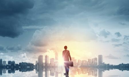 triunfador: Vista trasera del hombre de negocios mirando al atardecer por encima de la ciudad Foto de archivo