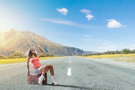 hitch hiker: Traveler woman sits on retro suitcase and waiting for car Stock Photo