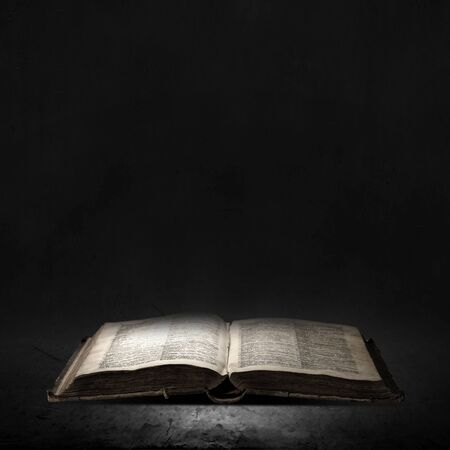 book concept: Opened book with light on pages on black background