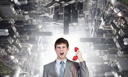important phone call: Angry businessman talking on red phone handset