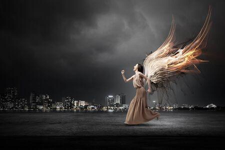 Aantrekkelijke vrouw die met engelenvleugels achter rug loopt