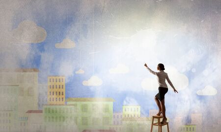 achieve: Businesswoman standing on chair and reaching hand to touch something Stock Photo