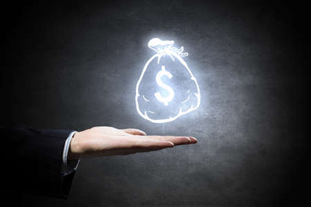money symbol: Hand of businessman holding money bag symbol on dark background