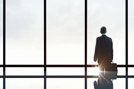 new idea: Back view of businessman looking on sunrise in office window Stock Photo