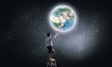 achieve: Businesswoman standing on chair and reaching Earth planet.  Stock Photo
