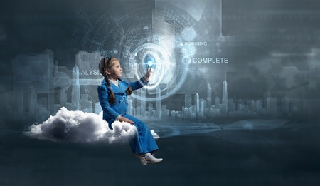 Little girl sitting on cloud and touching virtual panel with finger Stock Photo
