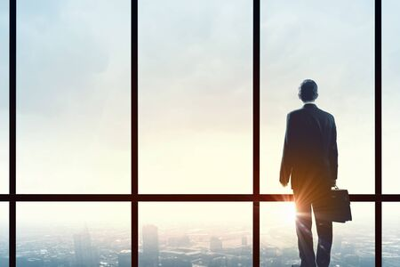 window view: Back view of businessman looking on sunrise in office window Stock Photo