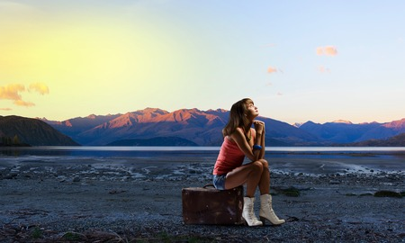 hitch hiker: Traveler woman sits on her retro suitcase outdoors Stock Photo